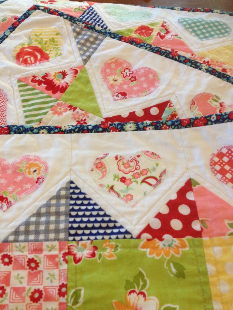 Detail of heart applique and binding on Oh So Pretty Quilt by Michelle Hickson